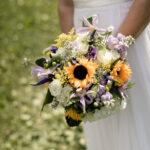 Bride holding Sunflower, lisianthus hydrangea bridal bouquet