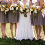 Bride and bridesmaids standing with sunflower and hydrangea bouquets