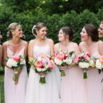 bride and friends smiling at each other holding their bouquets